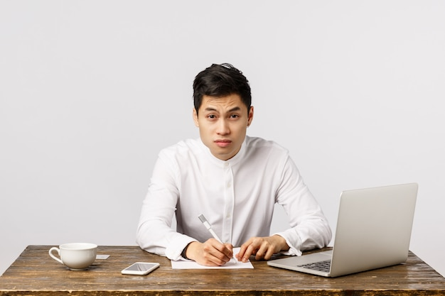 Tired and skeptical young asian male student trying take notes and catch lector speech, looking exhausted with sleepy eyes, squinting to clear view, sit desk with laptop, drink coffee, hardworking