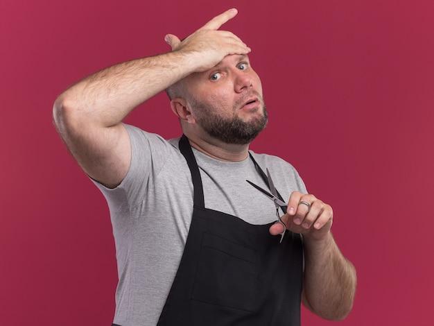 분홍색 벽에 고립 된 이마에 손을 넣어 가위를 들고 제복을 입은 피곤 슬라브 중년 남성 이발사