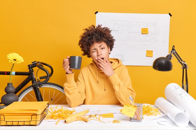 Tired sleepy afro american woman prepares for exams drinks coffee and yawns poses in coworking space. busy overworked female office worker finishes working on architect sketches. deadline concept