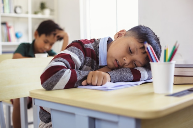 Tired and sleepy asian student during class lesson