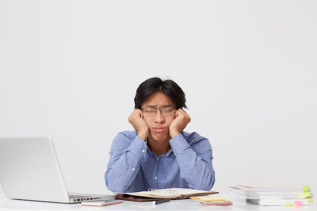 Tired sleepy asian young business man in glasses with head on hands sitting and sleeping at workplace at the table over white wall