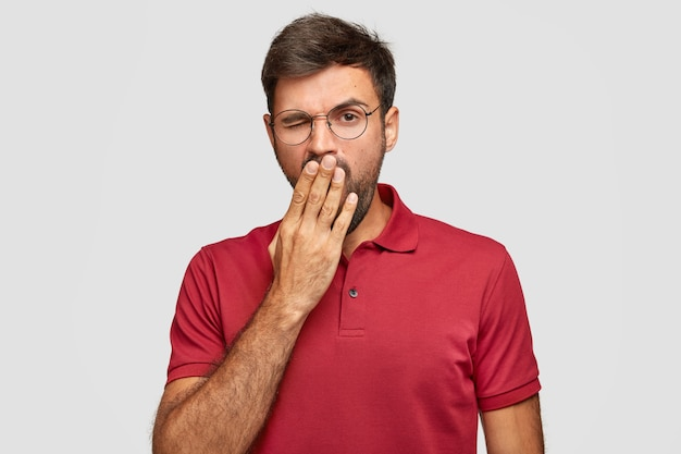 Tired sleepy bearded young male yawns, covers mouth with palm, wears spectacles and red t-shirt, stands against white wall, being fatigue after long work, isolated over white wall.