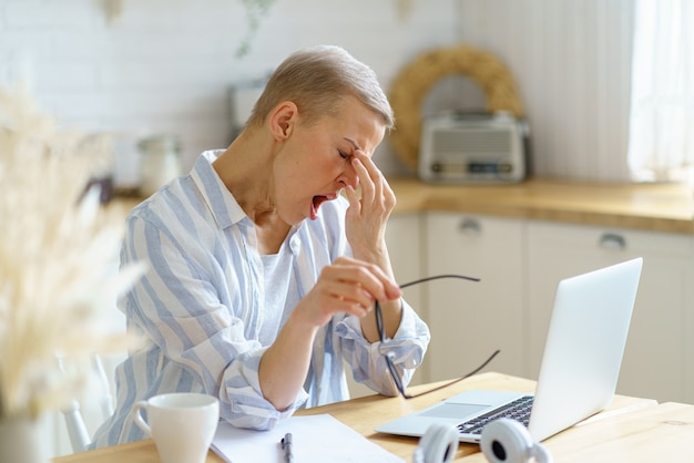 Tired sleepy middle aged woman massaging her nose and yawning while working on laptop online from