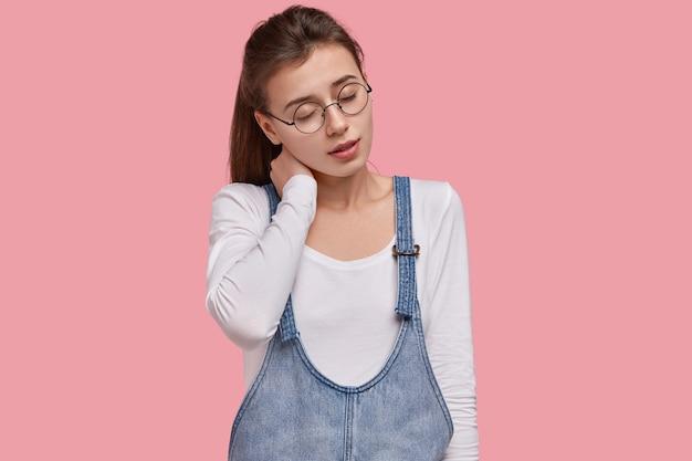 疲れた眠そうな女性は首に手を置き、休息を取りたい、不快感で目を閉じ、暗いポニーテールを持ち、視力が悪いので眼鏡をかけています
