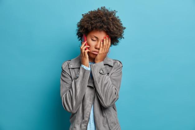 아프로 머리카락을 가진 피곤한 졸린 여성은 얼굴을 손바닥으로 만들고 피곤하고 피로감을 느끼며 지루한 전화 통화를하고 친구에게 전화를하고 회색 재킷을 입고 포즈를 취합니다.