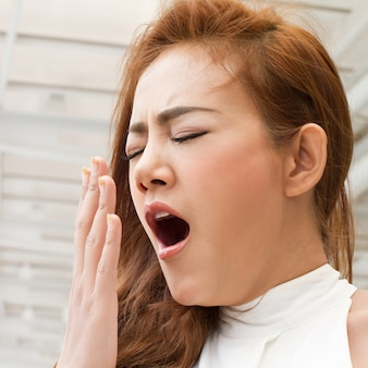 Tired, sleepy woman yawning with fatigue or insomnia