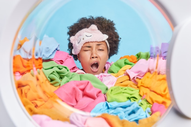 La donna stanca e assonnata sbadiglia dopo aver fatto il bucato sepolta in vestiti sporchi multicolori caricati nella lavatrice per il lavaggio
