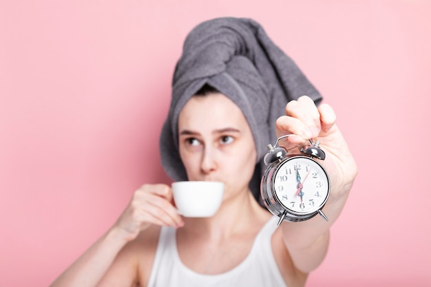 Tired and sleepy young girl drinks coffee in defocus and holds alarm clock in her hand on pink space. concept early morning rises, morning routine