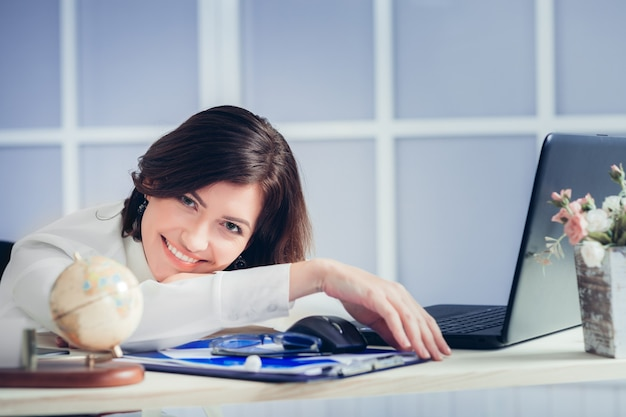 Tired smiling woman at the office desk in the evening
