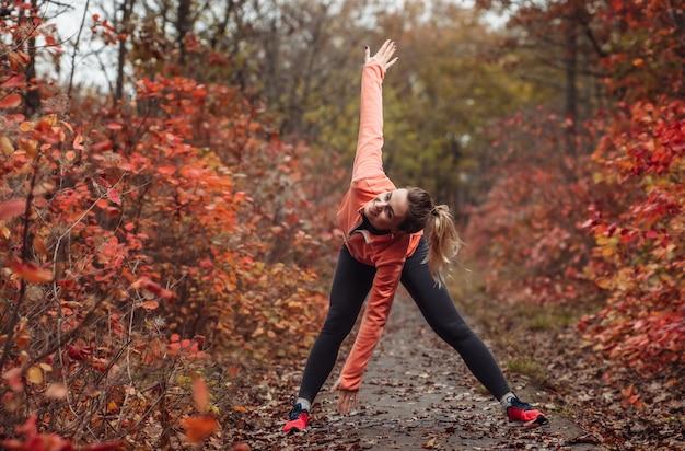 秋の森のスポーツウェアで疲れたスポーツ女性