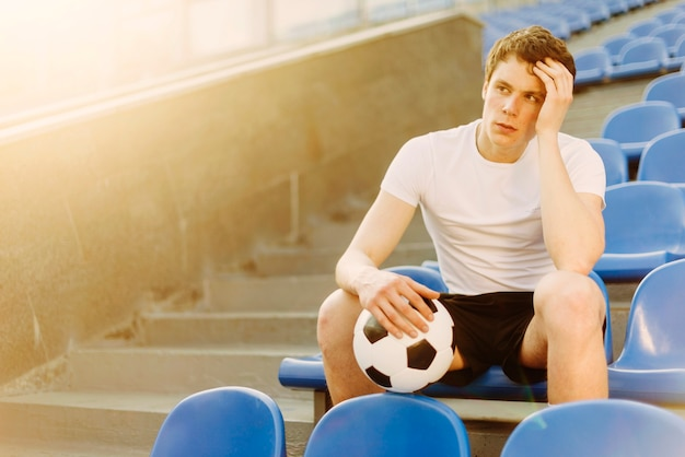 Tired sportsman with ball on stadium