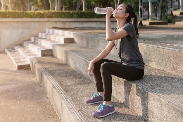 Tired sportswoman drinking water