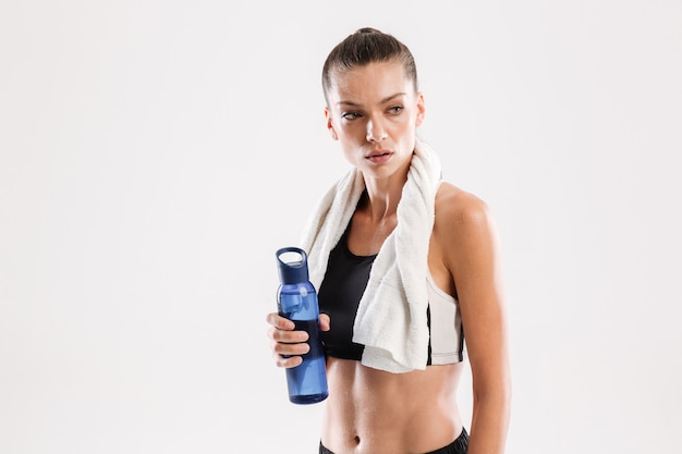 Tired sportswoman with towel on her neck holding water bottle