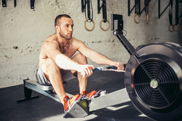 Tired sporty male workouts on power exercise machine in a gym club