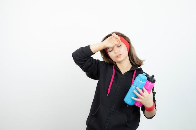 白い壁に水でボトルを保持している疲れたスポーティな女性。
