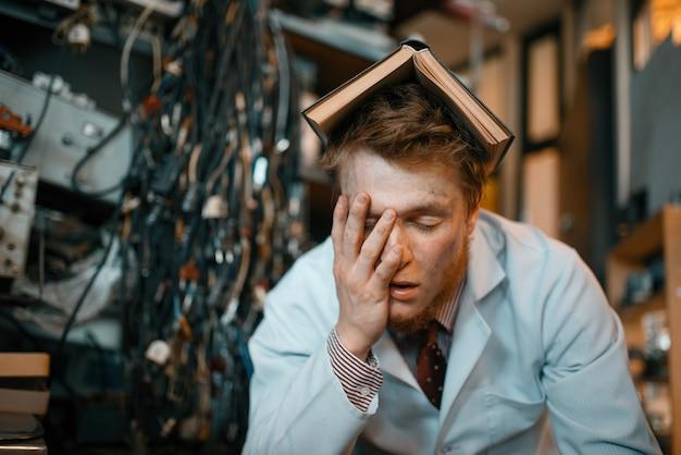 頭に本を持った疲れた奇妙なエンジニアが実験室で眠る。