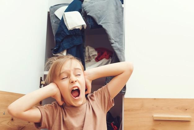 그의 옷장을 청소 피곤 스트레스 소년입니다. 옷장과 탈의실이 엉망입니다. 개념을 입을 아무것도. 옷장에서 옷을 찾는 어린 소년. 집안일 집안일.