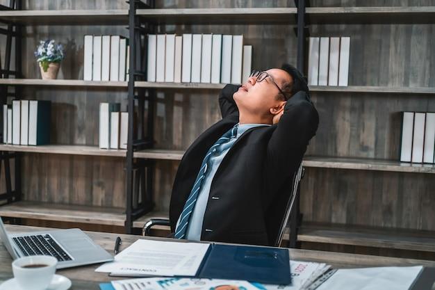 테이블에 앉아 사무실에서 일하는 목 통증으로 고통받는 피곤 스트레스 비즈니스 남자