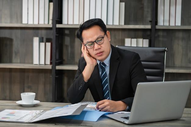 テーブルに座ってオフィスで働く首の痛みに苦しんでいる疲れたストレスの多いビジネスマン