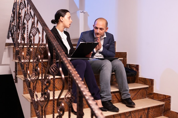 疲れたストレスの多いビジネスマンは、困難な専門的な仕事の締め切りの間に実業家の同僚と議論します。階段に座って企業の仕事で夜遅く一緒に働いている同僚の起業家、