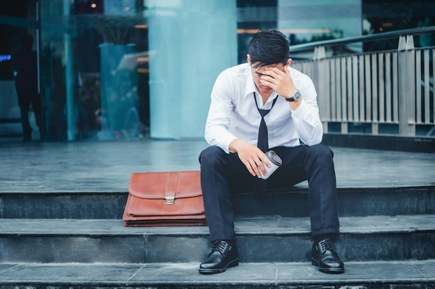 Tired or stressed businessman sitting on the walkway