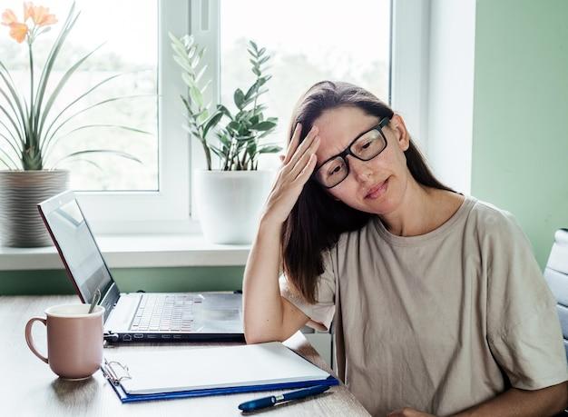 Усталая напряженная женщина в очках страдает от головной боли, работая из домашнего офиса, сидя за столом