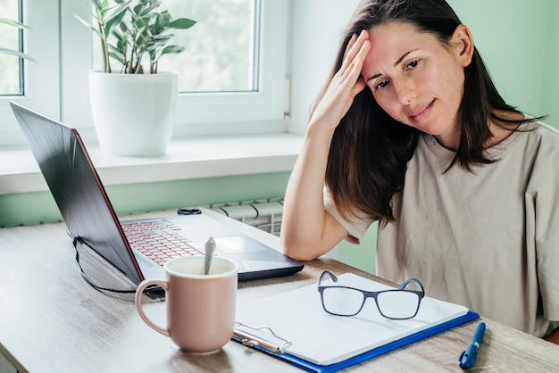 Усталая напряженная женщина, страдающая от головной боли, работает из домашнего офиса, сидя за столом