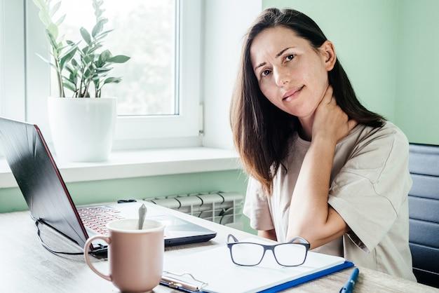 Усталая подчеркнула женщина, страдающая от боли в шее, работая из домашнего офиса, сидя за столом. переутомленная дама массирует шею, чувствуя боль от неправильной осанки