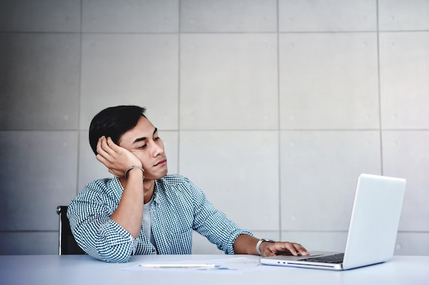 Tired and stressed young businessman sitting on desk in office with computer