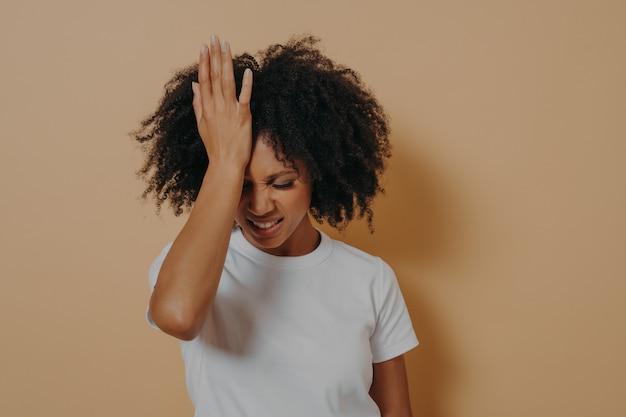 머리 편두통으로 고통받는 이마에 손을 대고 스트레스를 많이 받는 어두운 피부의 여성