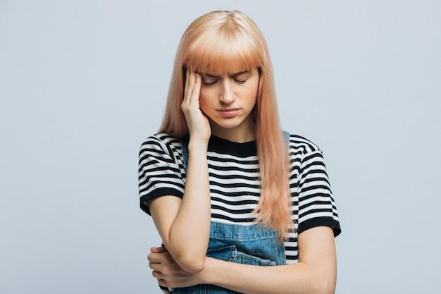 疲れたストレスの多い女性は頭痛があり、プレッシャーを感じ、集中しようとし、考えとともに集まり、神殿に手を伸ばします