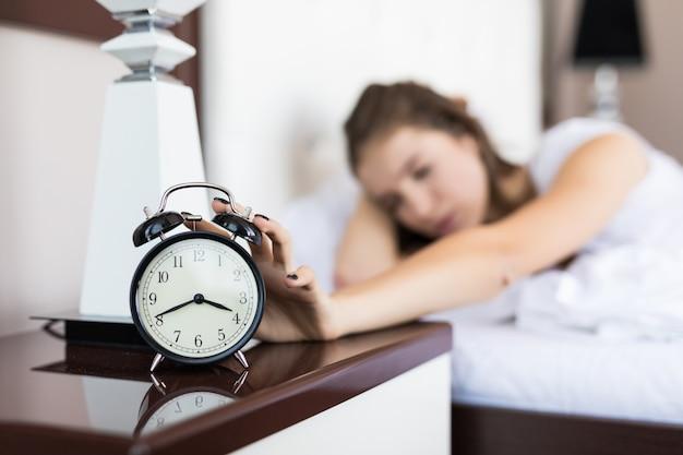 寝室で目覚まし時計が鳴るので疲れた学生ビジネスの女の子が朝目を覚ます