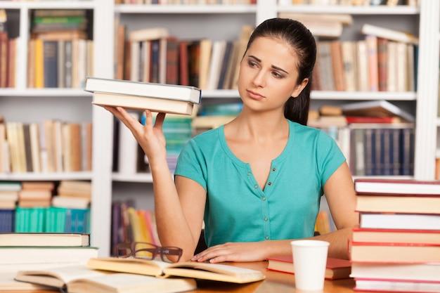 피곤한 학생입니다. 우울한 젊은 여성이 도서관 책상에 앉아 손에 책 더미를 들고 있다