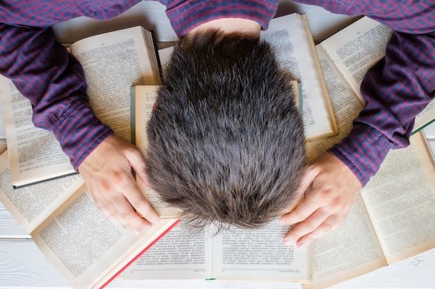 피곤한 학생이 책에서 잠들었습니다