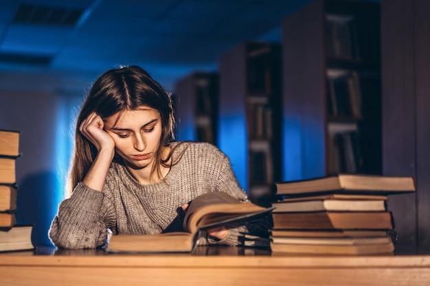 Утомленная девушка студента в вечере сидя полагаясь на его руке в библиотеке на столе с книгами. преподавание и подготовка к экзаменам