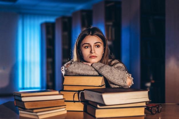 Утомленная девушка студента в вечере сидя полагаясь на его руке в библиотеке на столе с книгами. обучение и подготовка к экзаменам
