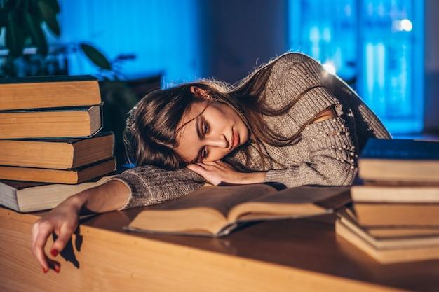 Утомленная студентка вечером спит в библиотеке за партой с книгами. преподавание и подготовка к экзаменам