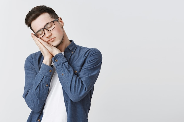 Tired student in glasses leaning on palms with closed eyes, sleeping