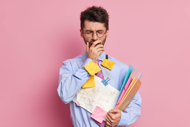 疲れた学生は眠そうな表情で口を手で覆い、フォーマルな服を着たあくびが試験ポーズの準備をします
