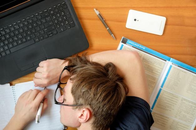 Усталый студент в очках спит на столе во время изучения английского языка плоской планировки