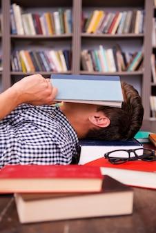 피곤한 학생입니다. 다른 책들이 주위에 놓여 있는 나무 바닥에 누워 있는 동안 책으로 얼굴을 덮고 있는 젊은 남자의 측면