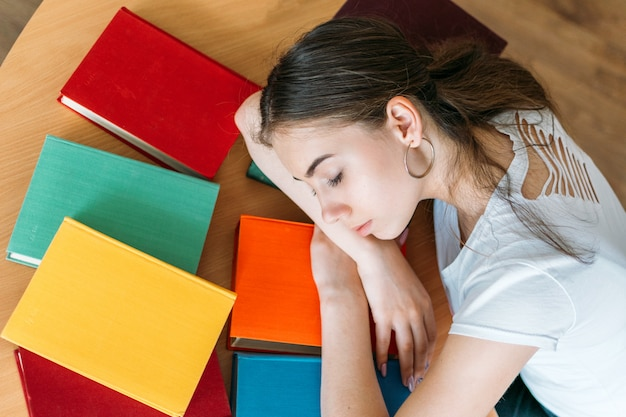 Tired student sleeping on book at library