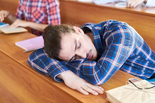 Tired student sleeping on desk