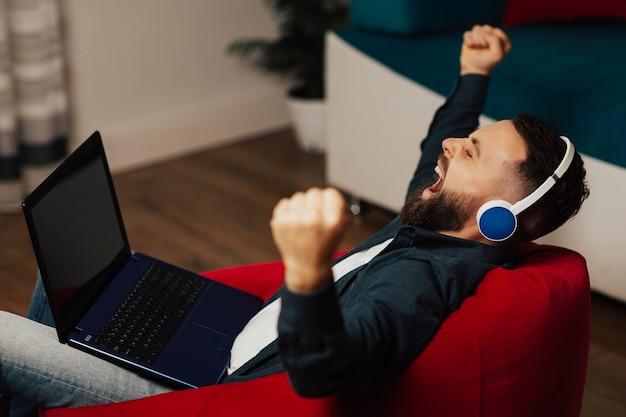 ヘッドフォンで疲れた学生は赤い肘掛け椅子に座って、オンラインで勉強した後あくびをします。