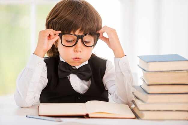 Tired of studying. tired little boy looking at the book and holding his glasses while sitting at the table