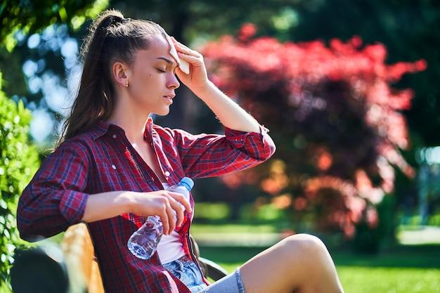 疲れた汗をかく女性はナプキンで額を拭き取り、暑い屋外で冷たい水ボトルを保持します