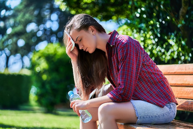Tired sweating woman with water bottle resting on a bench and wipes her forehead with a napkin in a park in summer hot weather