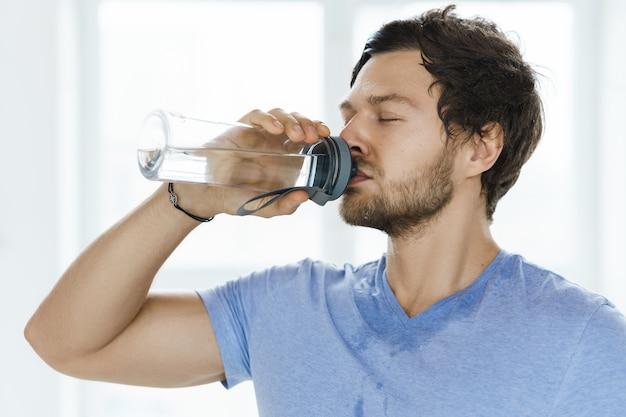피곤한 땀에 젖은 남자는 체육관에서 피트니스 운동 후 물을 마신다.