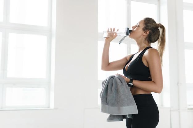 피곤한 땀에 젖은 여자는 체육관에서 열심히 피트니스 운동 후 물을 마신다.