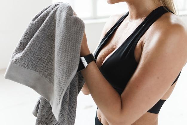 체육관에서 피트니스 운동 후 수건으로 피곤 땀에 젖은 여자